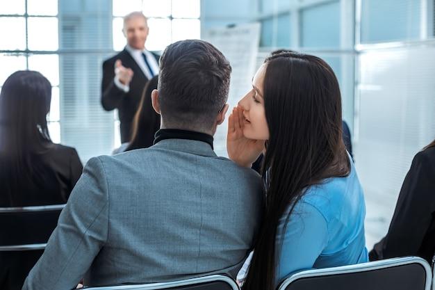 Visão traseira. colegas discutem algo durante uma apresentação de negócios