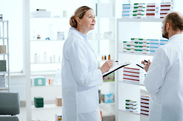 Visão traseira. dois boticários, homem e mulher, conversando, discutindo medicamentos.