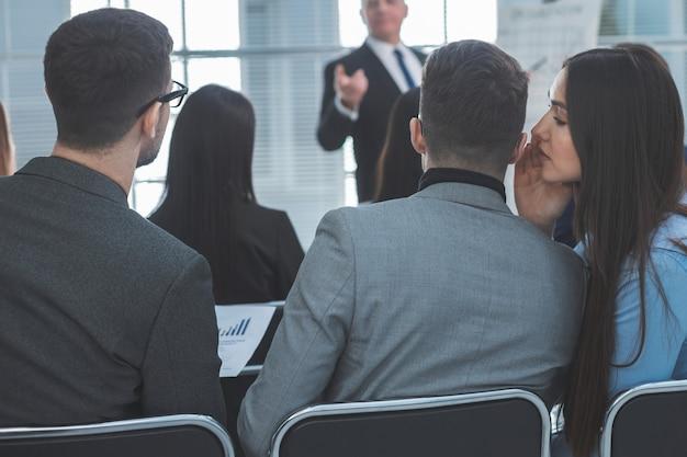 Visão traseira. funcionários discutem algo durante um seminário de negócios