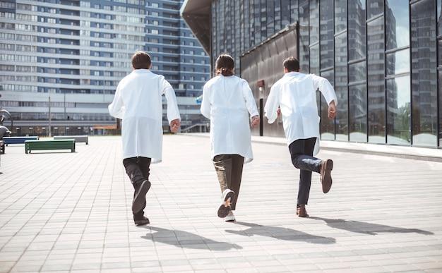 Visão traseira. grupo de médicos de resgate corre para prestar assistência de emergência