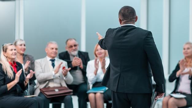 Visão traseira. o chefe está respondendo às perguntas da equipe durante o briefing