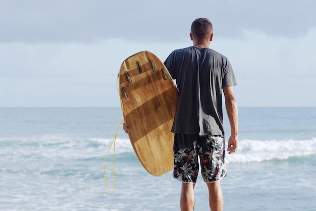 Visão traseira. surfista com prancha de surf, olhando para o oceano de manhã.