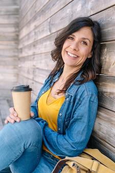 Visão vertical da bela mulher espanhola tomando café ao ar livre em um terraço ensolarado.