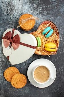 Visão vertical da caixa de presente com macarons e biscoitos, uma xícara de café no fundo escuro glacial