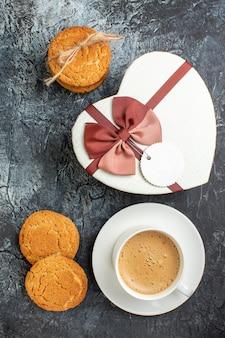 Visão vertical da caixa de presente e biscoitos, uma xícara de café no fundo escuro glacial
