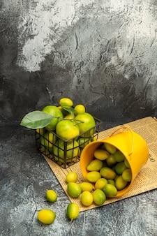 Visão vertical da cesta preta com tangerinas verdes frescas e balde caído com kumquats em jornais na mesa cinza