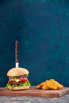 Visão vertical da faca em um saboroso sanduíche de carne e nuggets de frango na placa de madeira na superfície azul escura
