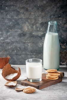 Visão vertical da garrafa de vidro e do copo cheio de leite na flor da bandeja de madeira em fundo escuro