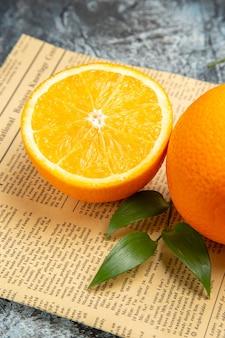 Visão vertical da laranja cortada ao meio e inteira com folhas no jornal em fundo cinza