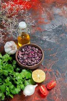 Visão vertical da preparação do jantar com alimentos e garrafa de óleo de feijão e um monte de tomate verde limão na mesa de cores misturadas