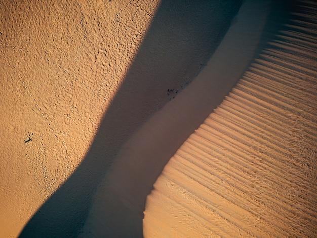 Visão vertical das dunas do deserto - conceito de destino de viagem de aventura selvagem e beleza do planeta na natureza intocada e ao ar livre