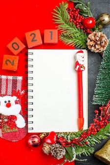 Visão vertical de acessórios de decoração de caderno espiral ramos de abeto xsmas números de meias em um guardanapo vermelho e árvore de natal em fundo escuro