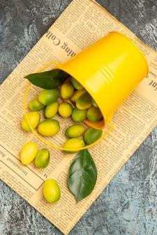 Visão vertical de balde amarelo caído com kumquats frescos em jornais em fundo cinza