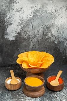 Visão vertical de batatas fritas crocantes decoradas em forma de flor e especiarias diferentes na mesa cinza