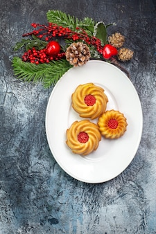 Visão vertical de biscoitos deliciosos em um prato branco e decoração de ano novo presente na superfície escura