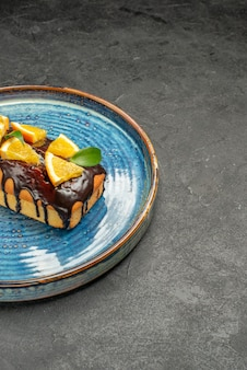 Visão vertical de bolo macio decorado com limão e chocolate em fundo escuro