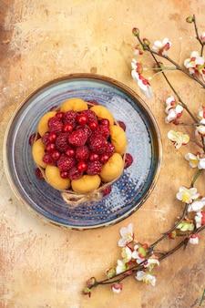 Visão vertical de bolo macio recém-assado com frutas e flores na mesa de cores misturadas