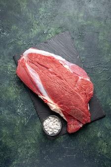 Visão vertical de carne vermelha fresca crua e sal na tábua de corte em fundo de cores preto e verde.