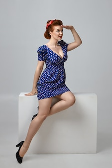 Visão vertical de corpo inteiro de uma glamourosa jovem europeia elegante com seios grandes e cabelos ruivos sentada confortavelmente, segurando a mão na testa, tentando ver algo à distância