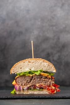 Visão vertical de corte de sanduíches saborosos na bandeja preta na superfície de cor escura