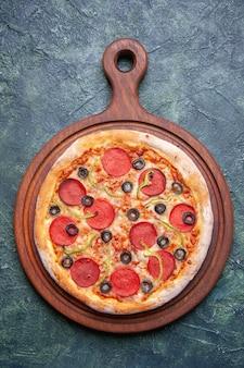Visão vertical de deliciosa pizza em uma tábua de madeira na superfície azul escura