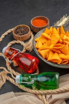 Visão vertical de deliciosas batatas fritas caídas de garrafas de pimentas na toalha e corda em um fundo preto