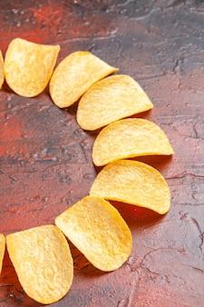 Visão vertical de deliciosas batatas fritas caseiras crocantes em fundo escuro com espaço livre