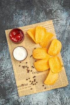 Visão vertical de deliciosas batatas fritas caseiras e ketchup de maionese na tigela de pimenta e molho no jornal na mesa cinza