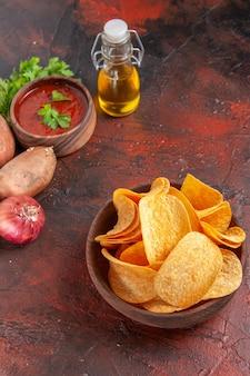 Visão vertical de deliciosas batatas fritas caseiras em uma pequena tigela marrom, alho, ketchup verde, batatas, cebola, óleo, garrafa, ligado, dark table