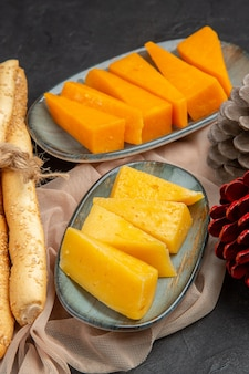 Visão vertical de deliciosas fatias de queijo e cones de coníferas em uma toalha em um fundo preto