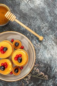 Visão vertical de deliciosas panquecas de frutas e mel