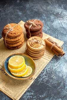 Visão vertical de deliciosos biscoitos de canela e limão empilhados em um jornal velho sobre fundo escuro