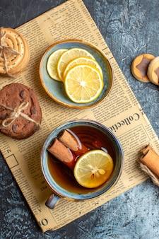 Visão vertical de deliciosos biscoitos e uma xícara de chá preto com canela em um jornal velho sobre fundo escuro
