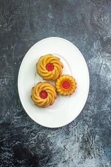 Visão vertical de deliciosos biscoitos em um prato branco na superfície escura