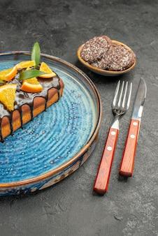 Visão vertical de deliciosos bolos e biscoitos com garfo e faca em fundo preto