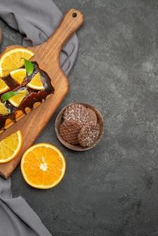 Visão vertical de deliciosos bolos macios cortados limões com biscoitos na tábua de madeira