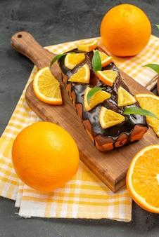 Visão vertical de deliciosos bolos macios inteiros e limões cortados com folhas na mesa escura