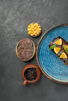 Visão vertical de deliciosos bolos na bandeja azul e biscoitos em fundo escuro