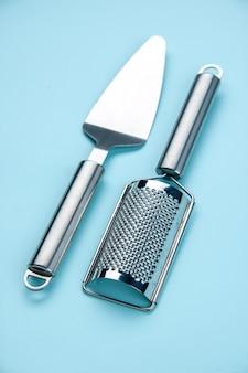 Visão vertical de dois utensílios de cozinha de aço inoxidável no fundo da onda azul
