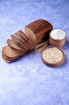 Visão vertical de fatias de pão preto com farinha de aveia no fundo azul claro com espaço livre