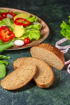 Visão vertical de fatias de pão preto de vegetais frescos picados em um prato e mede o pacote verde na superfície de cores escuras