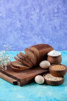Visão vertical de fatias de pão preto picado ao meio em tábuas de madeira farinha de aveia de trigo em tigelas ovos de flores sobre fundo azul claro