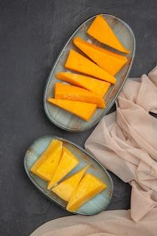 Visão vertical de fatias de queijo saboroso em uma toalha em um fundo preto