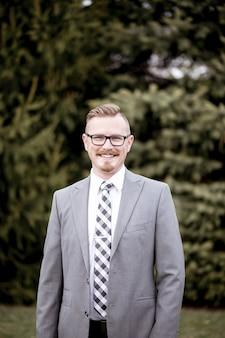 Visão vertical de foco raso de um homem vestindo um terno cinza e óculos enquanto sorria para a câmera