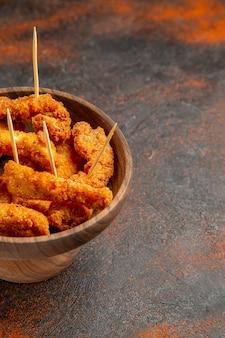 Visão vertical de frango frito crocante no meio de cores misturadas