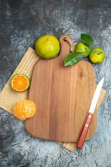 Visão vertical de frutas cítricas frescas com folhas ao redor da tábua de madeira cortadas ao meio e uma faca no jornal sobre fundo cinza