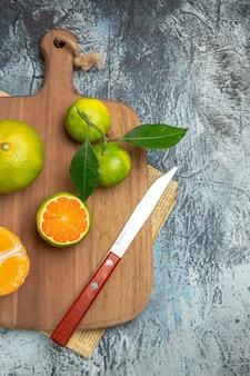 Visão vertical de frutas cítricas frescas com folhas na tábua de madeira cortadas ao meio e faca no jornal sobre fundo cinza