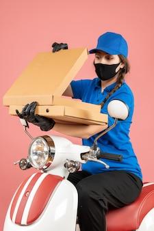 Visão vertical de jovem mensageira confiante usando máscara médica e luvas abrindo caixas em pêssego pastel