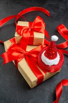 Visão vertical de lindos presentes com fita vermelha e chapéu de papai noel na mesa escura
