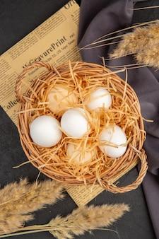 Visão vertical de muitos ovos orgânicos em uma toalha preta em uma superfície escura